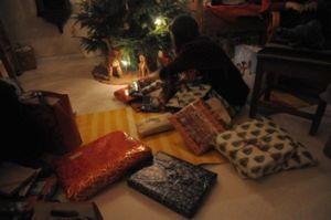 Lapsi joulukuusen alla ja vierellä paljon joululahjoja