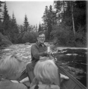 Mies ja lapset veneessä