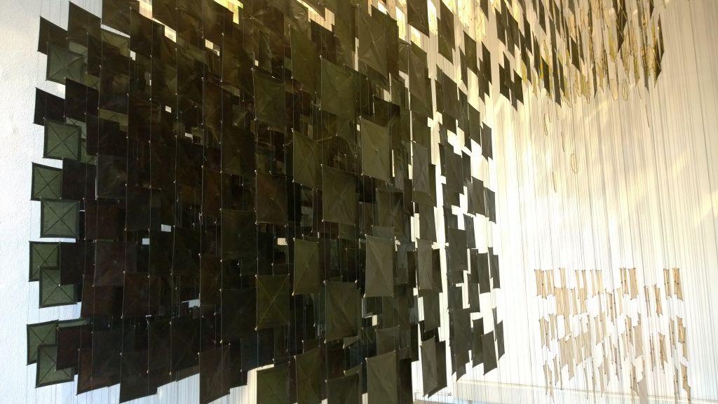 Artikkelin kuvituksena on taidenäyttelyssä otettu kuva. Siinä näkyy osa nykytaideteoksesta. Teos koostuu rykelmästä mustia ja rykelmästä valkoisia neliöitä, jotka riippuvat nauhoina katosta.