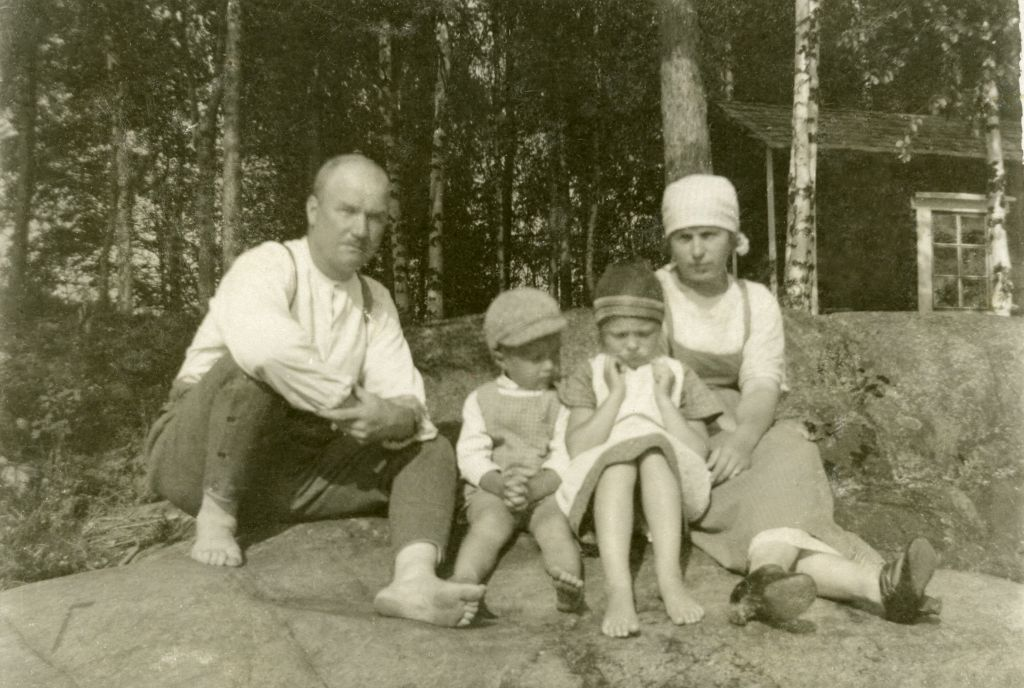 Mies, kaksi lasta ja nainen kalamajan edustalla. Vanha, mustavalkoinen kuva.