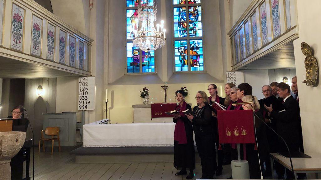 Kuoro laulaa Vehmaan kirkon kuorissa. Kanttori säestää flyygelillä.
