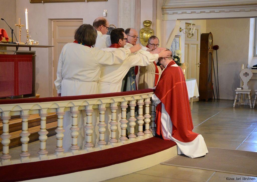 Kirkkoherra Tolvanen polvistuneena alttarille, siunauksen toimittajat pitävät käsiä hänen päänsä päällä