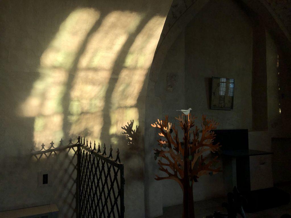Valo heijastuu ikkunasta kirkon kiviseen seinään. Etualalla metallinen aita ja kastepuu.