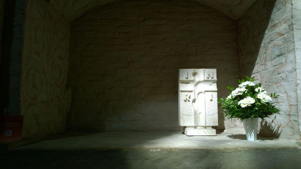 Pyhän Henrikin hautakomero Turun tuomiokirkossa: holvattu syvennys valkeaksi kalkitussa tiiliseinässä. Oikeassa reunassa on kimppu valkoisia kukkia valkeassa maljakossa ja sen vieressä, vasemmalla puolella jalustan varassa seisova valkea suorakaiteen muotoinen ristireliefi.