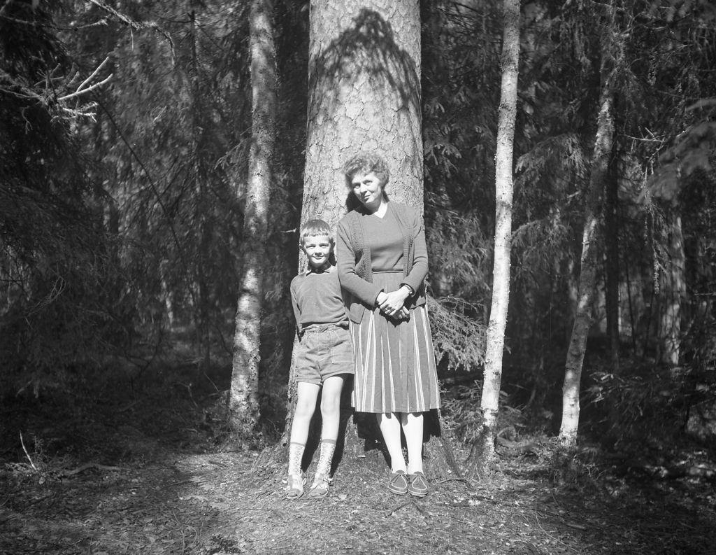 Äiti ja poika nojaamassa puunrunkoon