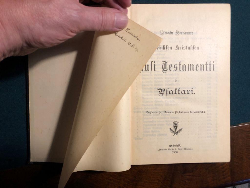 Käsi selaa avoimen kirjan nimilehteä