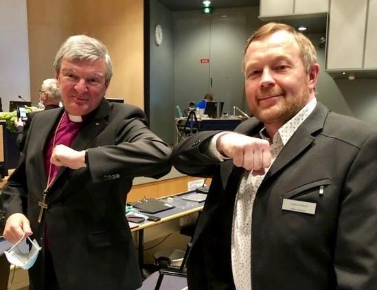 Piispa Kaarlo Kalliala ja kirkolliskokousedustaja Pekka Heikkilä tervehtivät kyynärpäitä koskettelemalla elettä liioitellen.