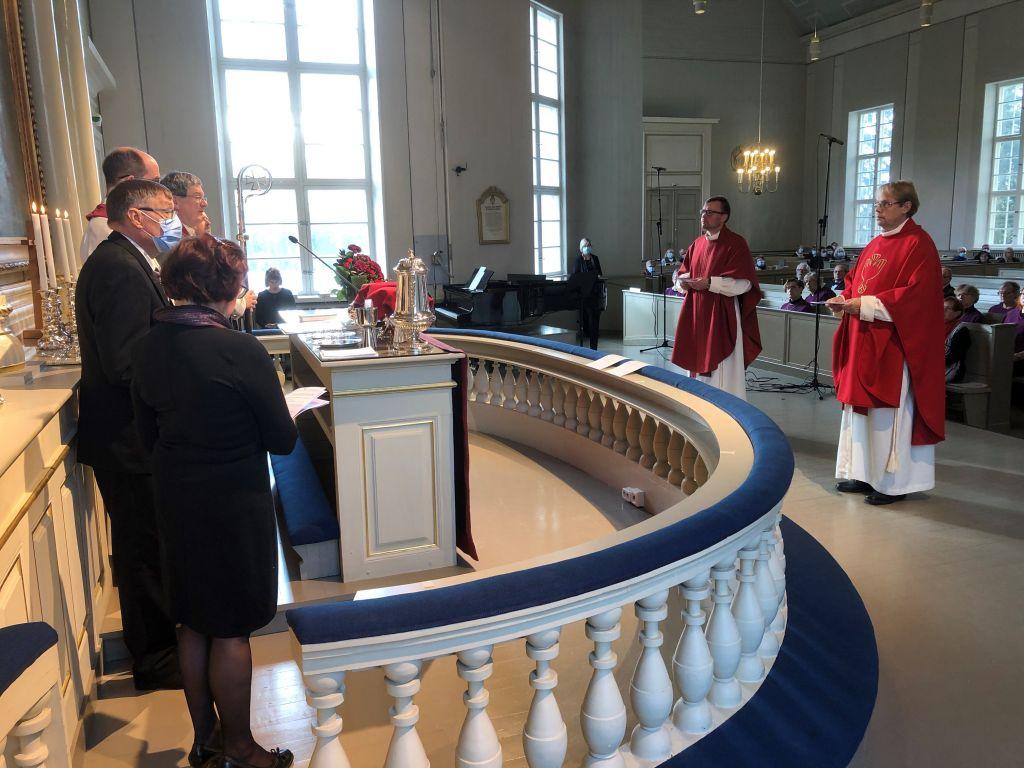 Virkaan asetettavat kirkkoherra Mika Kyytinen ja kappalainen Jaakko Rainerma kuuntelevat piispa Kallialan puhetta kirkon alttarikaiteen edessä seisten, kumpikin punaiseen kasukkaan puettuna.