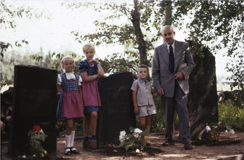 Kuvassa vanha mies haudalla kolmen lapsen kanssa