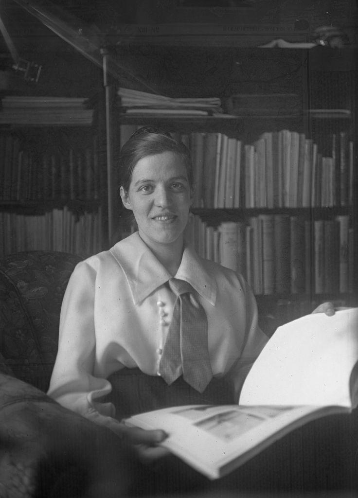 Mustavalkoisessa kuvassa nainen kirja kädessään kirjahyllyn edessä.