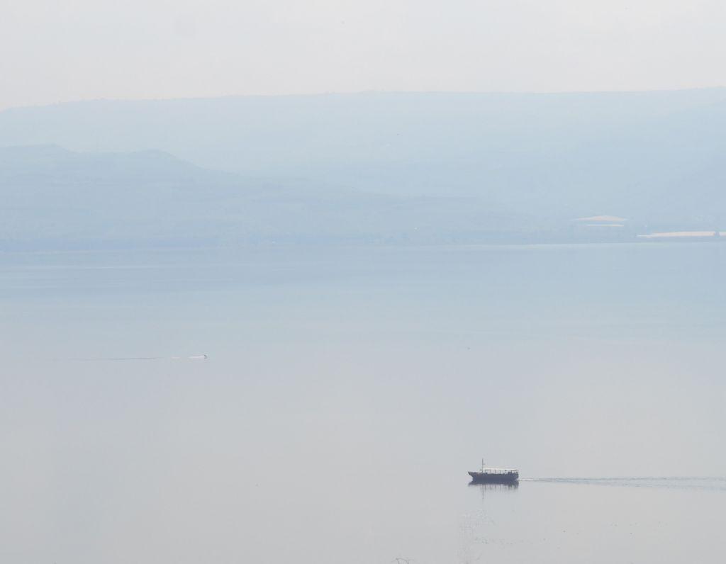 Vene lipuu sumuisella Gennesaretinjärvellä. Taustalla siintävät sinertävinä vuoret.