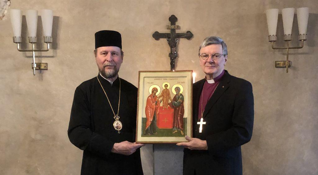 Kuvassa piispa Arseni ja piispa Kalliala pitävät käsissään ikonia. Taustalla risti seinässä.